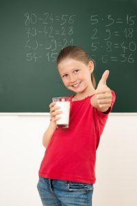Schülerin zeigt Daumen hoch und in anderer Hand ein Glas Milch
