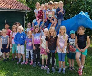 Kinder sitzen auf einer großen blauen Plastikkuh