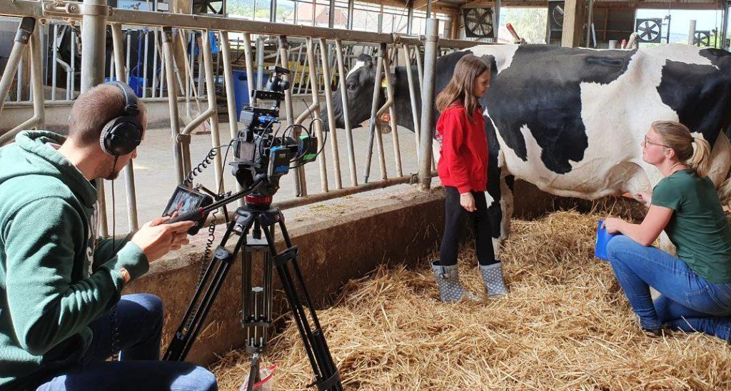 Kinderreporterin Vitoria lässt sich von Henriette an einer Kuh das Melken früher erklären.
