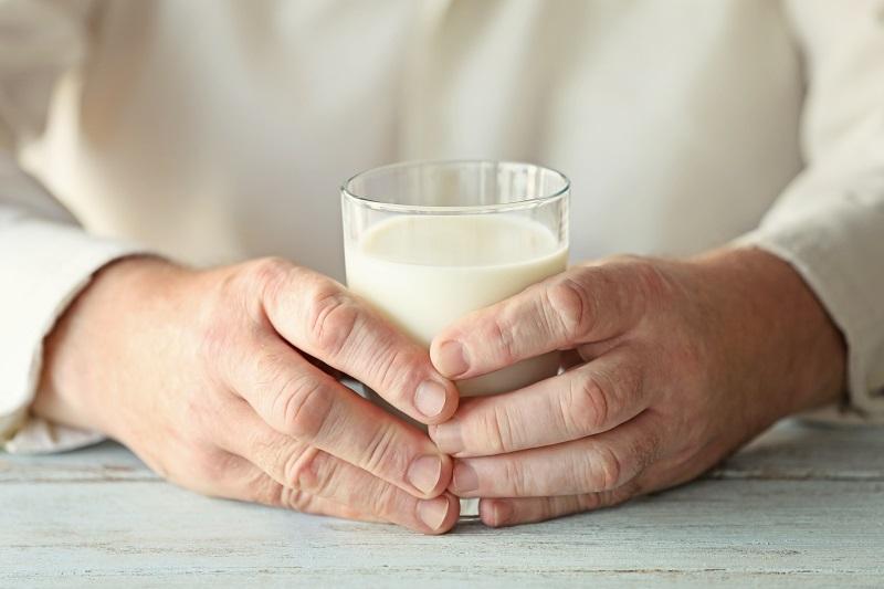 Hände halten ein Glas Milch