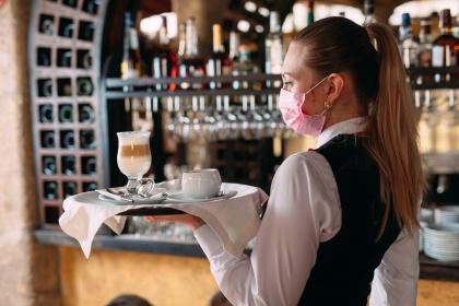 Kellnerin serviert Kaffee auf Tablett im Café