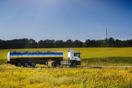 Milchsammelwagen auf Landstraße umgeben von Rapsfeldern