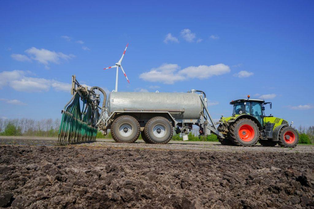 Traktor auf Ackerfeld bei Gülleausbringung
