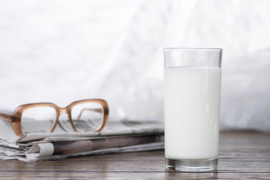 Ernährungsvorträge: Milchglas auf Holzuntergrund vor Zeitung und Brille