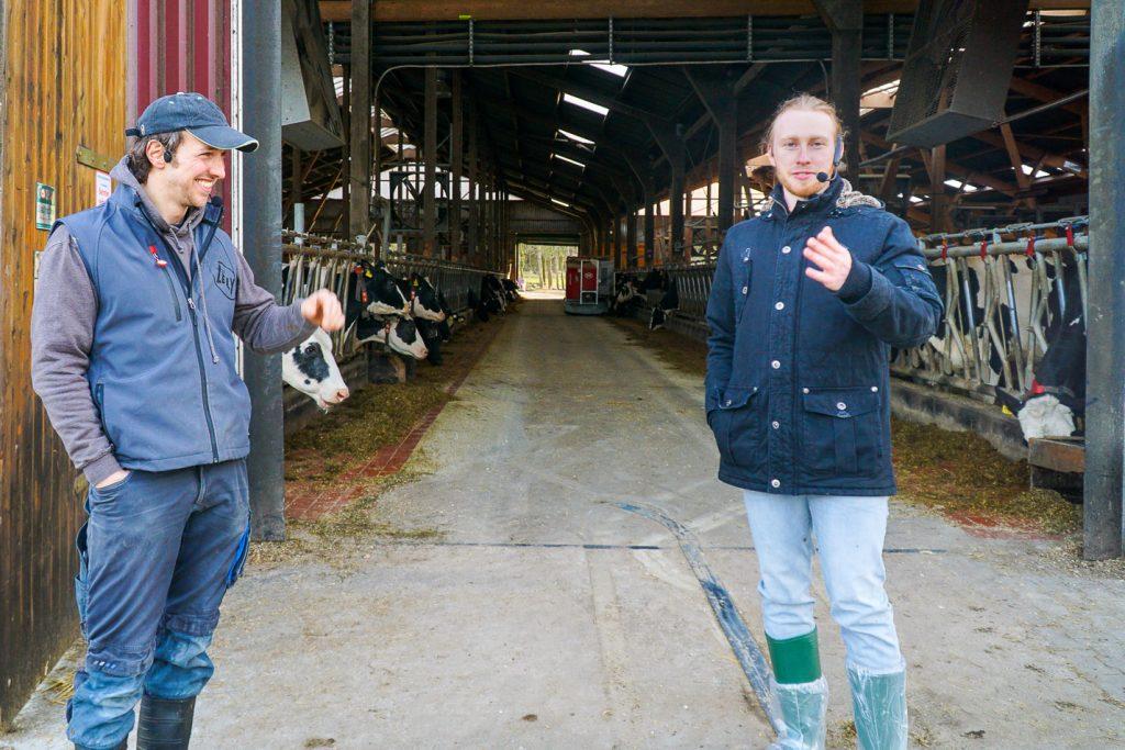 Timo und Sven vorm Kuhstall mit selbstfahrender Fütterungsanlage