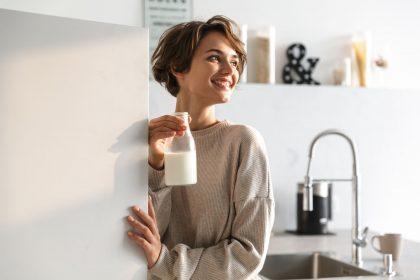 Frau mit Milchflasche in Küche