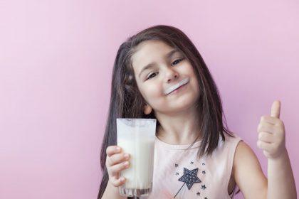 Mädchen mit Milchschnute, die Daumen hoch zeigt und Milchglas in der Hand hält
