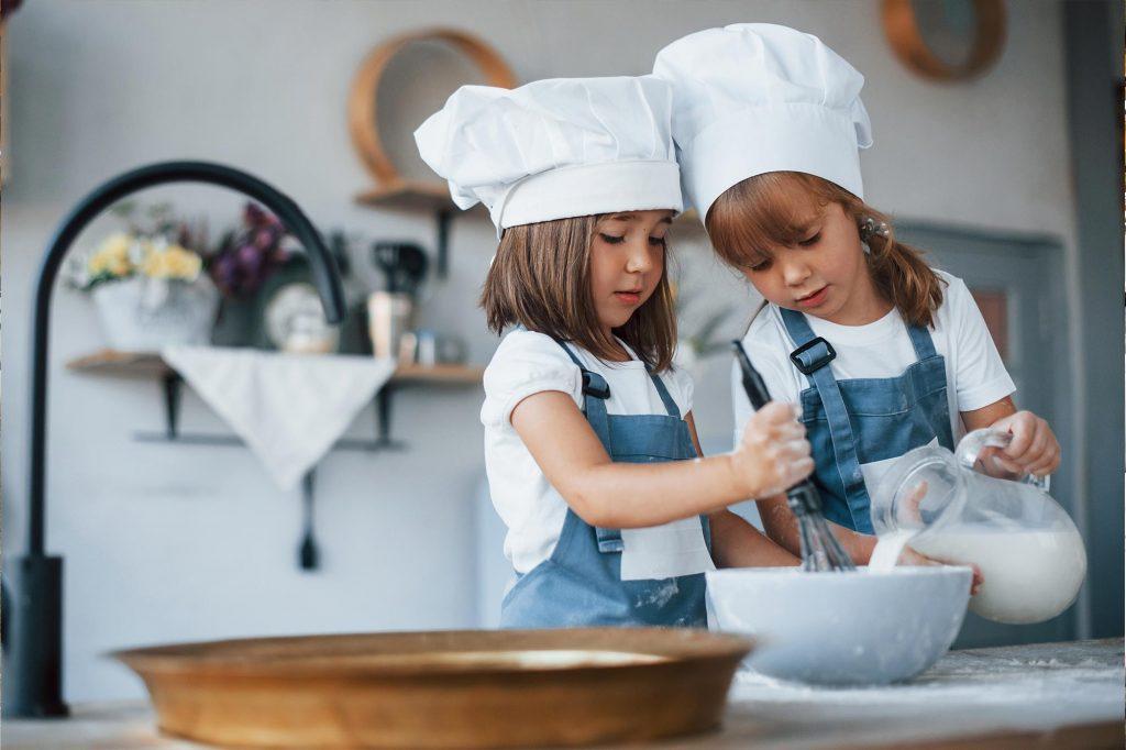 Kita Kinder mit Kochmützen beim Backen