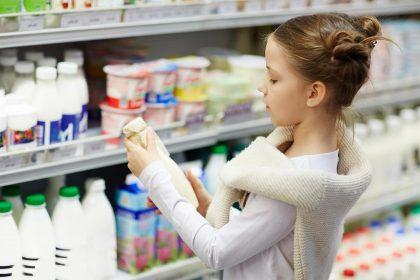 Mädchen mit Milch vor Supermarktregal im Lebensmitteleinzelhandel