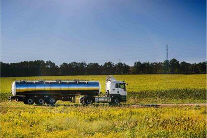 Milchsammelwagen fährt zwischen Rapsfeldern