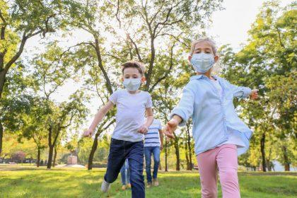 Kinder bewegen sich mit Maske